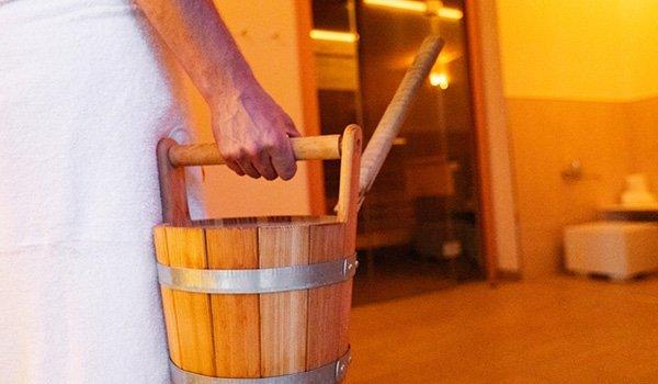 Mann geht in die Saune mit Eimer Wasser